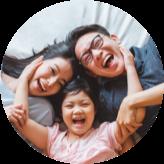 Famille de trois personnes allongées sur le dos sur un lit et riant vers la caméra