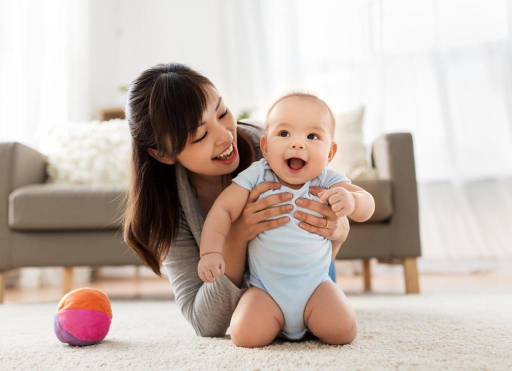 Bébé riant tout en étant retenu par sa mère