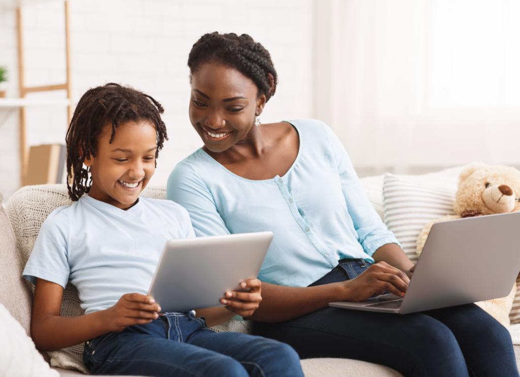 Garçon d'âge scolaire montrant à sa mère quelque chose sur un iPad