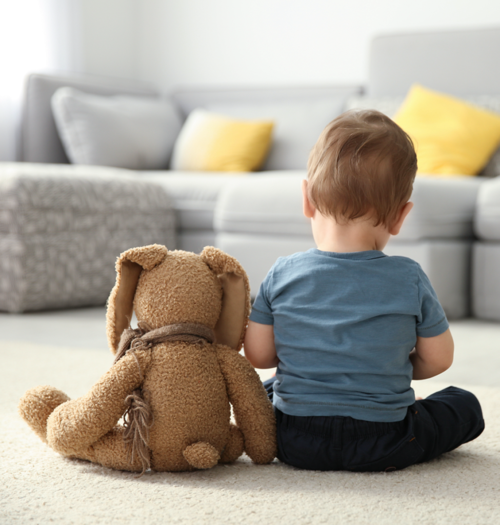 Toddler and his teddy bear sitting on the ground facing away from the camera