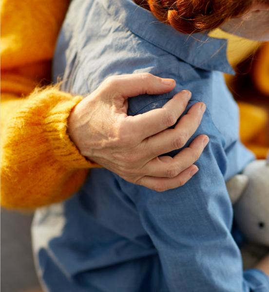 Gros plan d'une adulte avec sa main autour d'une fillette rousse
