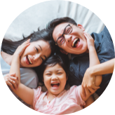Family of three laying on their back on a bed and laughing toward the camera