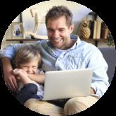 Garçon d'âge primaire et son père assis sur un canapé en regardant un ordinateur portable