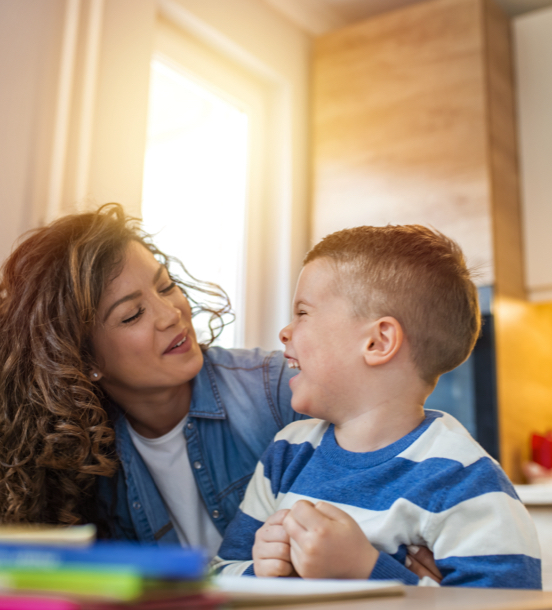 Preschool aged boy laughing with a young woman in a sunny room