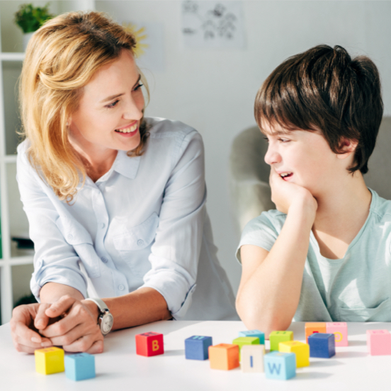 Woman and boy sitting at table with colourful blocks