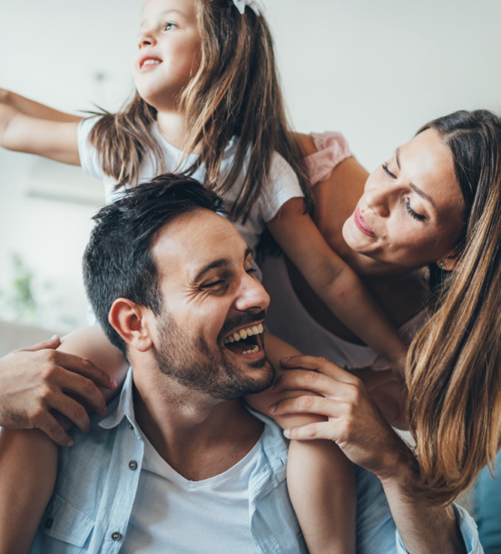 Family of 3 laughing together with dad giving a piggy back ride
