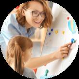 Une jeune femme montrant du doigt un dessin que regarde un enfant