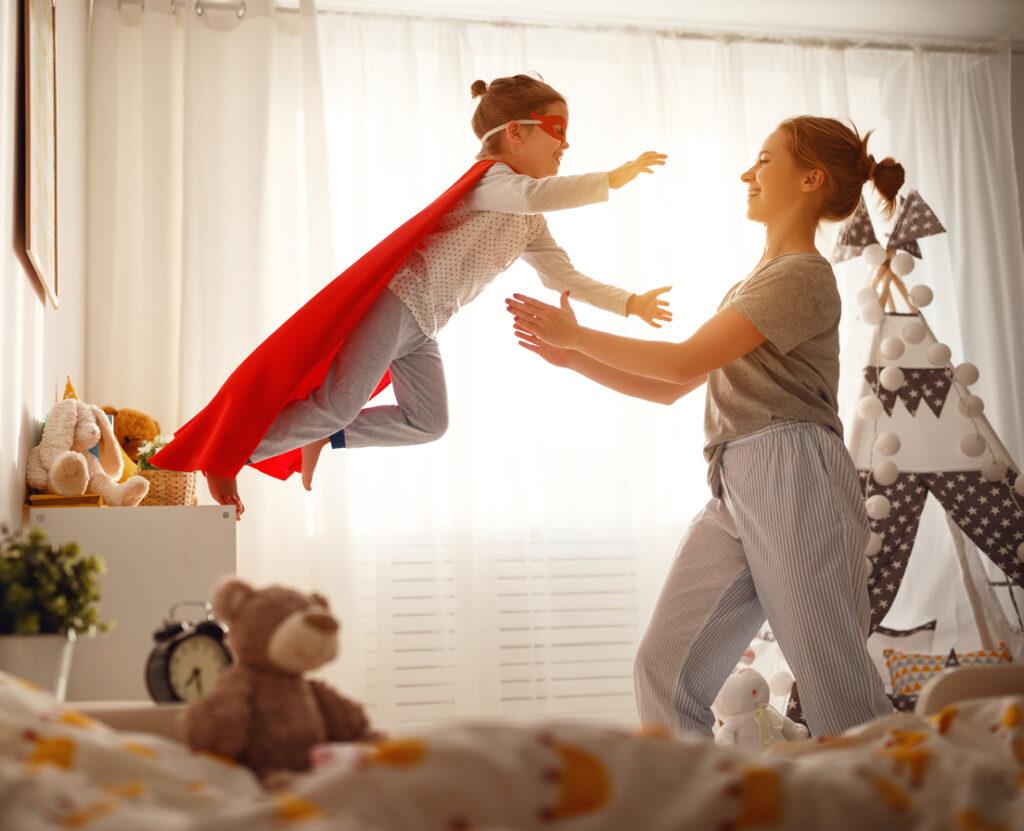 Jeune enfant en cape de super-héros sautant vers une jeune femme